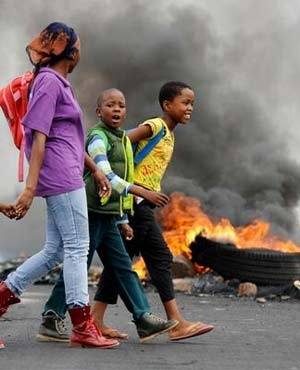 A woman walks with children past a burning tyre following protests in Hebron. (Herman Verwey, Beeld)