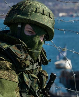Russian soldiers guard a pier where two Ukrainian naval ships are moored, in Sevastopol, Ukraine. (Andrew Lubimov, AP)