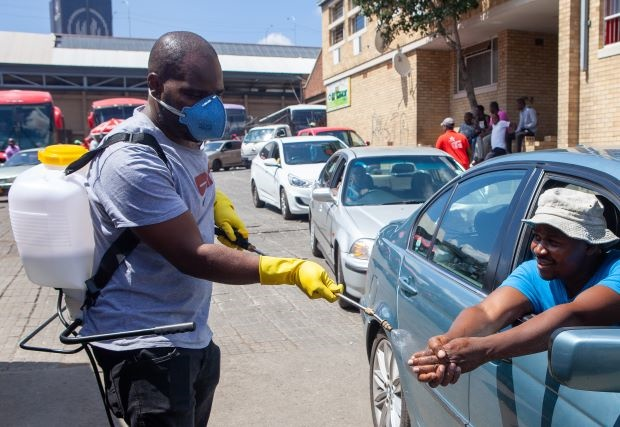 People sanitising their hands with a spray at Fleet Africa Bus Rank in Johannesburg.  (Photo by Gallo Images/Papi Morake)