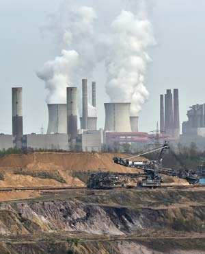Giant machines dig for brown coal at the open-cast mining Garzweiler in front of a smoking power plant near the city of Grevenbroich in western Germany where the IPCC is currently conducting talks on climate change. (Martin Meissner, AP)