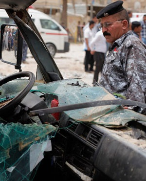 Iraqi security forces and civilians inspect the site of a parked car bomb attack at a commercial area in the southern city of Najaf, 160km south of Baghdad, Iraq. (File, AP)
