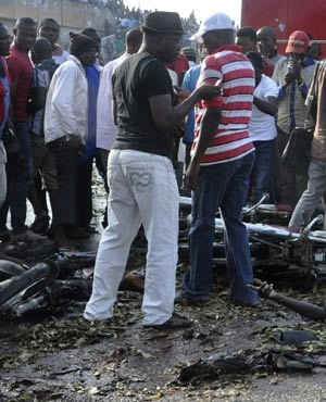 People gather at the site of a blast at the Nyanya Motor Park, Nigeria. (Gbemiga Olamikan, AP)