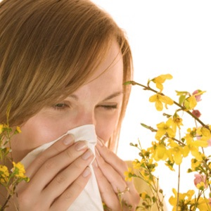 Woman with hay fever allergy blows nose