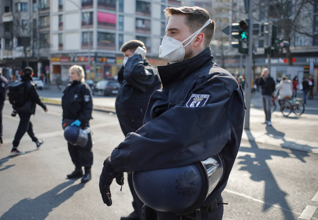 Police officers wear face masks as they surround a spontaneous rally in Berlin's Kreuzberg district on March 28, 2020, amid the novel coronavirus Covid-19 pandemic.
