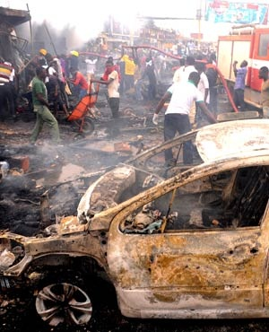 Firefighters and rescuers extinguish a fire at the scene of a bomb blast at Terminus market in the central city of Jos. AFP)