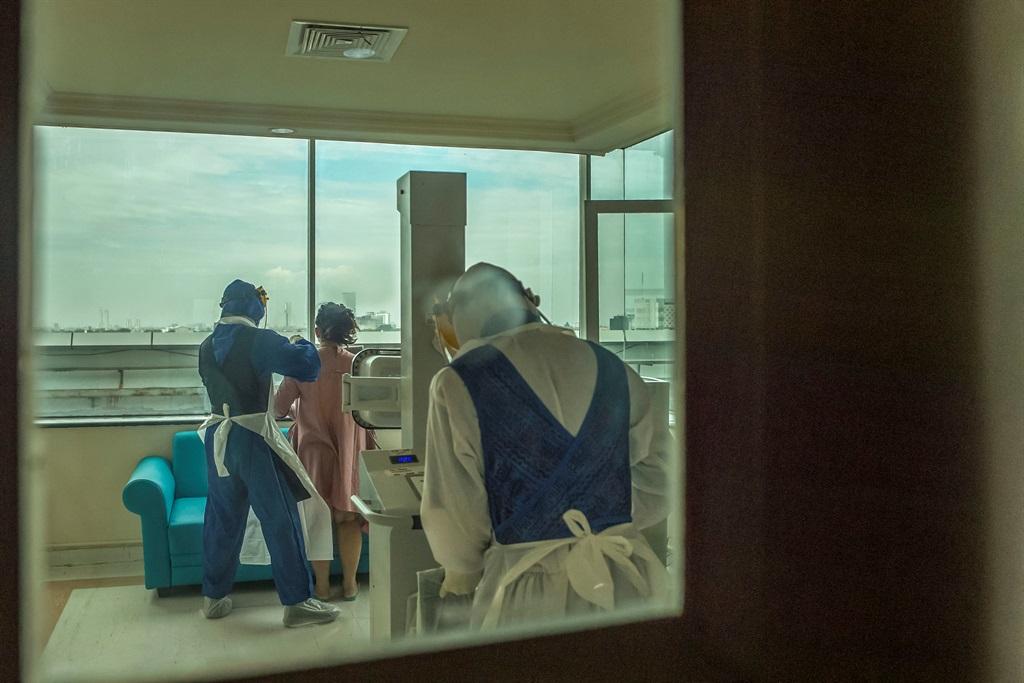 Health workers help a COVID-19 coronavirus patient (C) at Husada Utama hospital in Surabaya, East Java, on July 8, 2021. (JUNI KRISWANTO / AFP)
