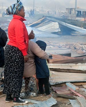 People watch as their dwellings are dismantled in Lwandle, near Cape Town. (Rodger Bosch, AFP)
