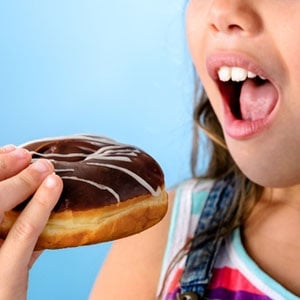 A girl about to take a bite of a chocolate donut from Shutterstock.
