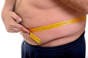 Obese man measuring his belly overweight from Shutterstock