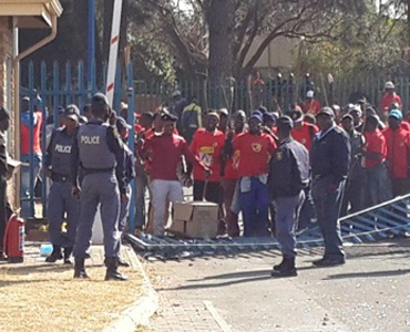 A Fin24 user sent an image of protesters forcing down a fence during the recent Numsa strike while SAPS officers stand by. (Supplied)
