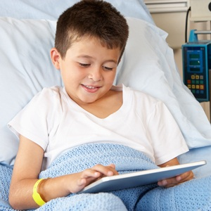 Boy in hospital bed with digital tablet from Shutterstock
