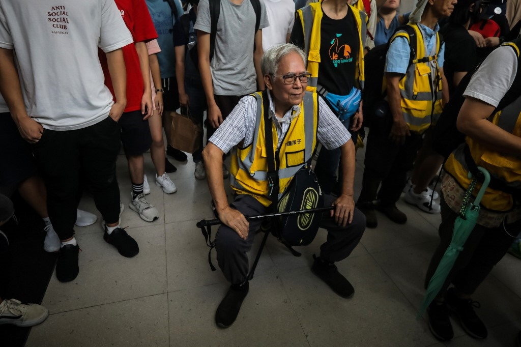"""Grandpa Wong"" (C), 85, taking a rest on a portable stool set up in between a group of protesters in the Tung Chung district in Hong Kong."