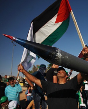 A masked youth carries a rocket during a celebration by the Muslim Brotherhood movement to declare the victory of Gaza and Hamas against Israel. (AP Photo/Mohammad Hannon)