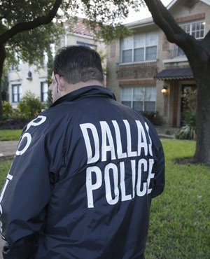 Police stand guard outside the  hospital worker's home. (Roger Steinman, AP)