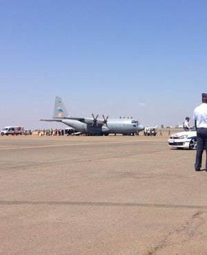 Members of ministerial task team, including Jeff Radebe, stand round the aircraft. (Erin Bates, Twitter)