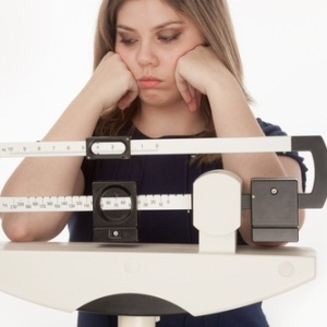 Young woman and scale from Shutterstock