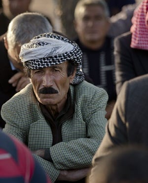 Kurdish mourners sit during the funeral of Ahmed Mustafa, a People's Protection Units fighter who died after being injured while fighting ISIS forces in the Syrian city of Kobani. (Vadim Ghirda, AP)