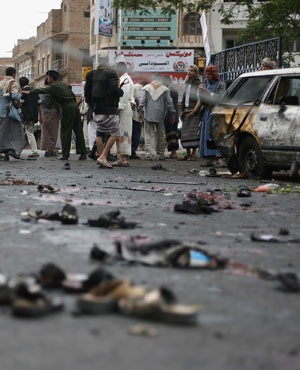People gather at the site of a suicide bombing as Yemeni security officials collect debris in Sana'a, Yemen. (AP Photo)
