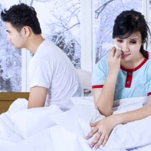 Woman crying in bed from Shutterstock