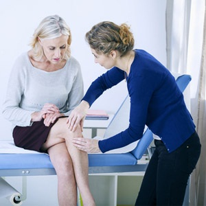 Senior woman consulting with a doctor about her joint pain.