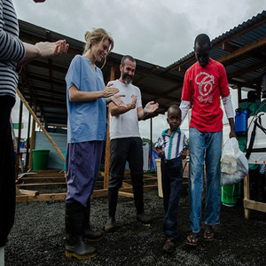 Six-year-old Patrick Poopei and his father William walk out of the Ebola Treatment isolation unit in Monrovia, Liberia. Both are now Ebola survivors.