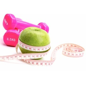 An apple, a measuring tape and dumbbell