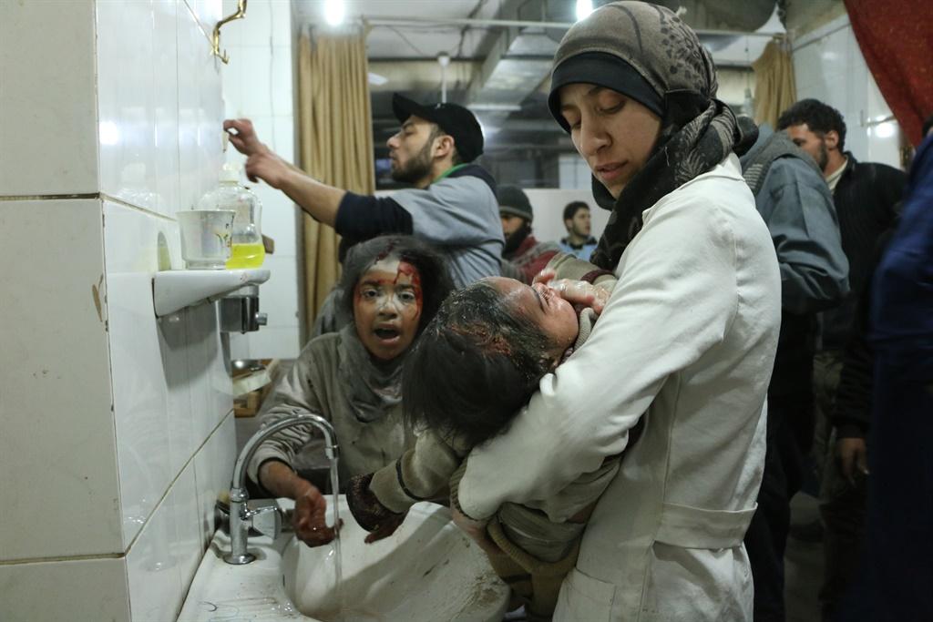 Al Ghouta, Syria - Dr. Amani (R) treats an injured