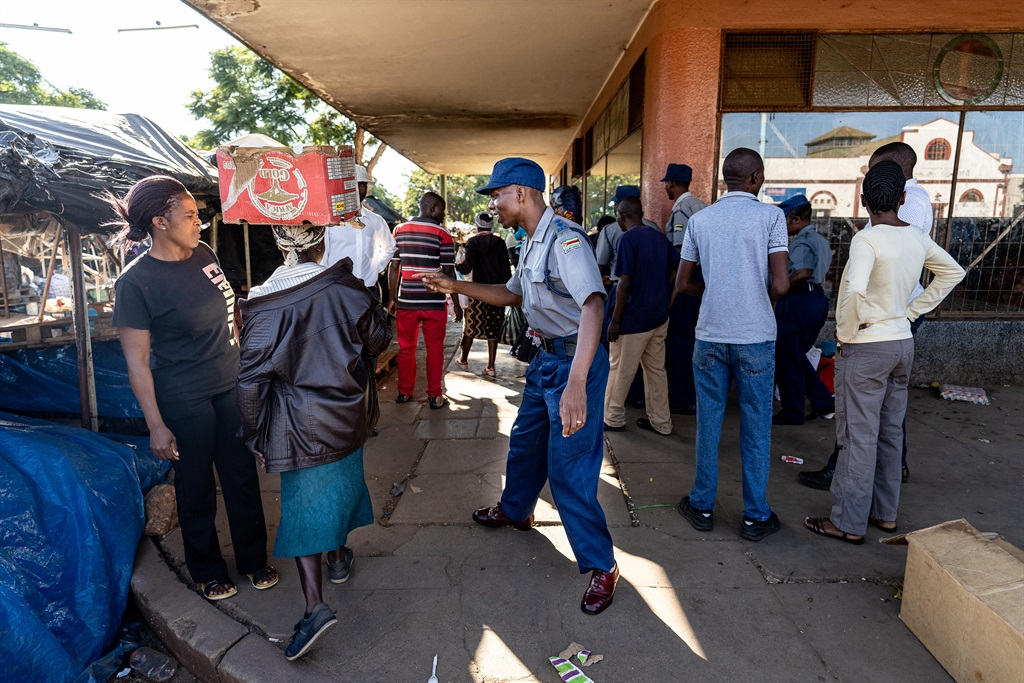 A police officer orders a vendor to leave after stocking fresh produce from a vegetable market in Bulawayo, Zimbabwe.