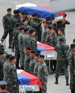 Philippine police commandos carry the flag-draped coffins of their fallen comrades from C-130 planes shortly after arriving at a military base in Manila. (Ted Aljibe, AFP)