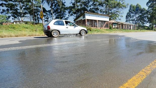 A vehicle drives through a river of water from a burst pipe on Sweetwaters Road.