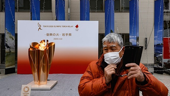 A man wearing a face mask stands in front of the Tokyo 2020 Olympic flame being displayed outside Miyako railway station, Iwate prefecture on 22 March 2020, after arriving from Greece. Photo: Philip FONG / AFP
