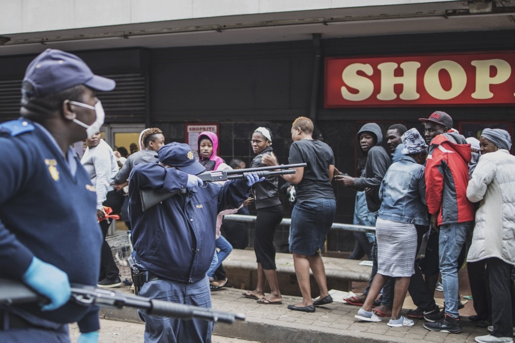 A South African policeman points his pump rifle to disperse a crowd of shoppers in Yeoville, Johannesburg. (Marco Longari, AFP)