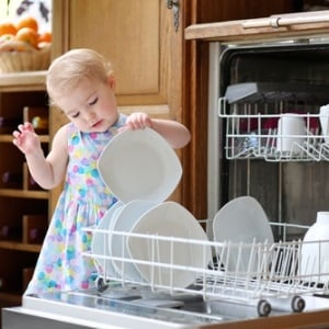 Child takes plates out of dishwasher
