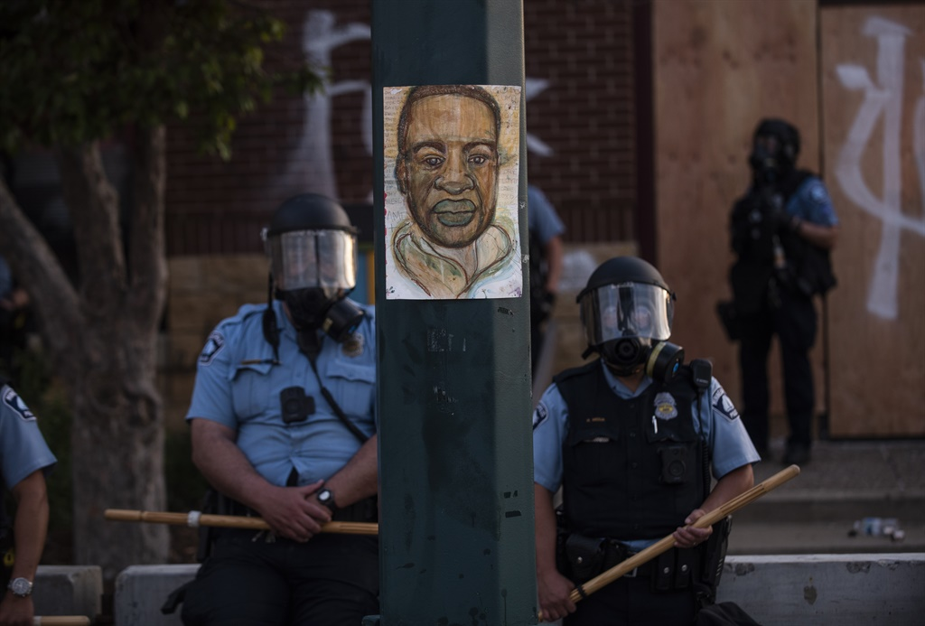 A portrait of George Floyd hangs on a street light pole as police officers stand guard at the Third Police Precinct during a face off with a group of protesters on May 27, 2020 in Minneapolis, Minnesota.