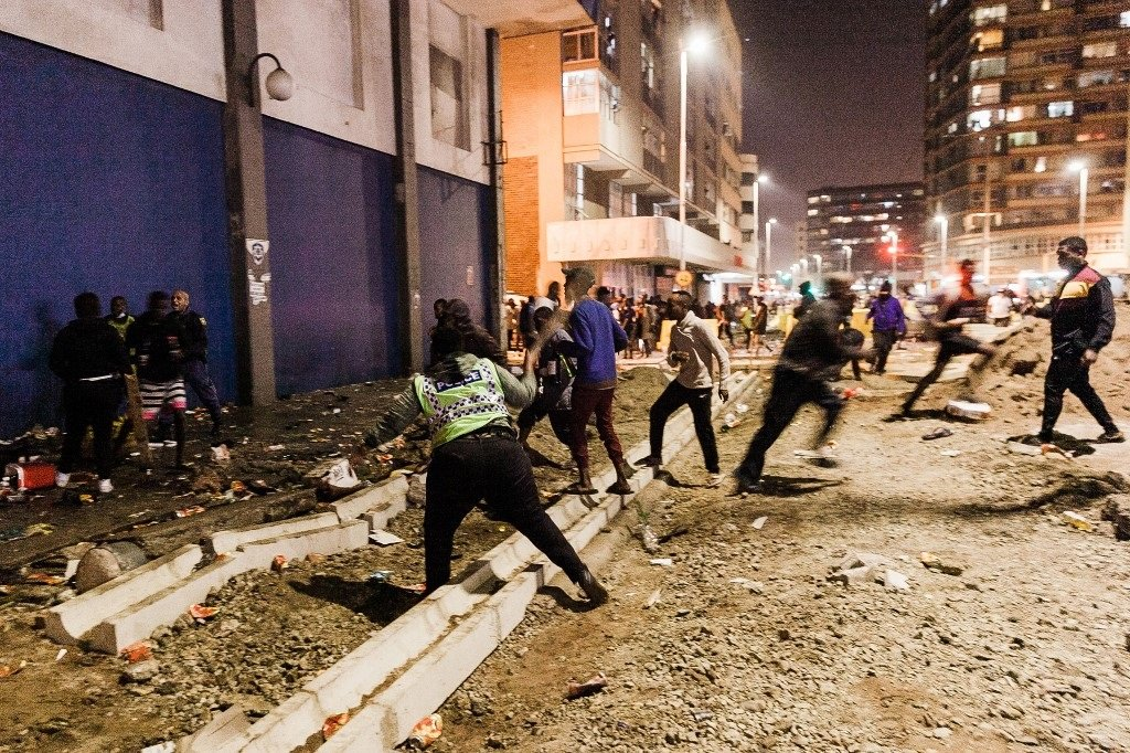 Police officers stop people from looting in central Durban.