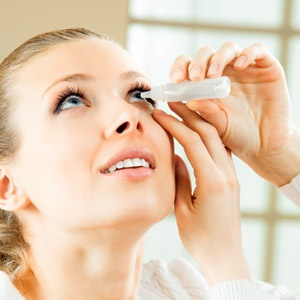 Lady using drops for dry eyes caused by pollen
