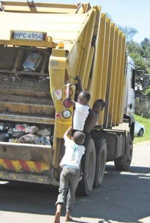 Children hang onto a refuse removal truck in Copesville. (Nalini Naidoo, The Witness)