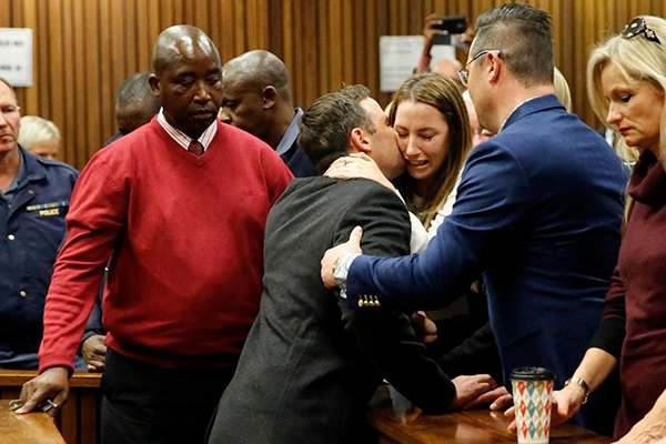 Oscar Pistorius holds his sister Aimee Pistorius as he leaves the High Court in Pretoria, after being sentenced to six years in jail for murdering his girlfriend Reeva Steenkamp three years ago. (AFP)