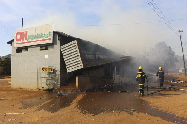 Firefighters extinguish a fire at a supermarket during eSwatini protests.