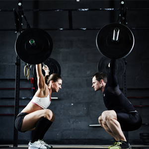 Man and woman lifting weights in gym