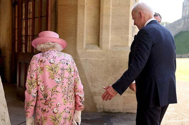 US President Joe Biden (R) walks with Britain's Qu