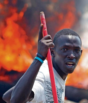 A protester stands in front of a burning barricade during a protest in Burundi's capital, Bujumbura. (AP)