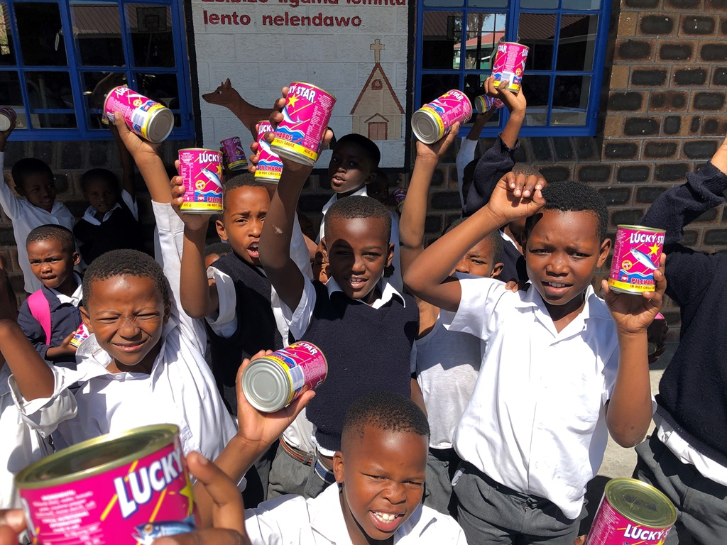 Happy children receiving cans of food