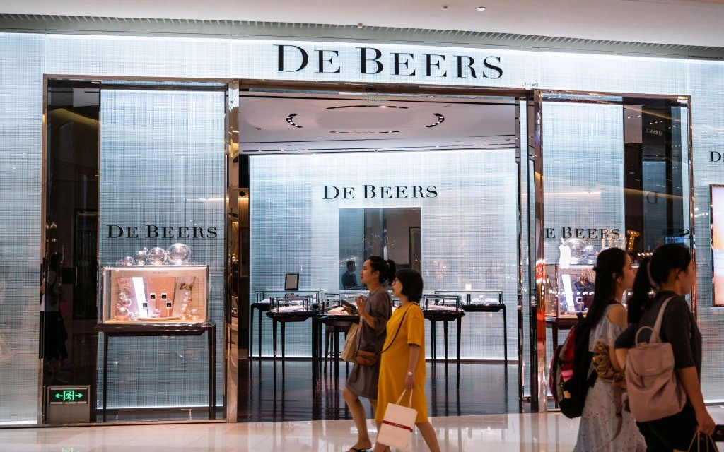 Pedestrians pass by a De Beers store in Shanghai.