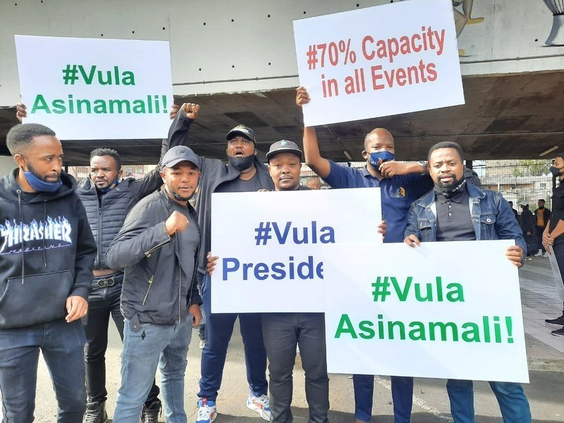 """Dressed in all black, the artists held up placards that read """"#Vula Asinamali"""", """"#70 Capacity in all events"""", and """"#Vula President"""". (Instagram/ Sifiso Kalinjani Mdunge)"""