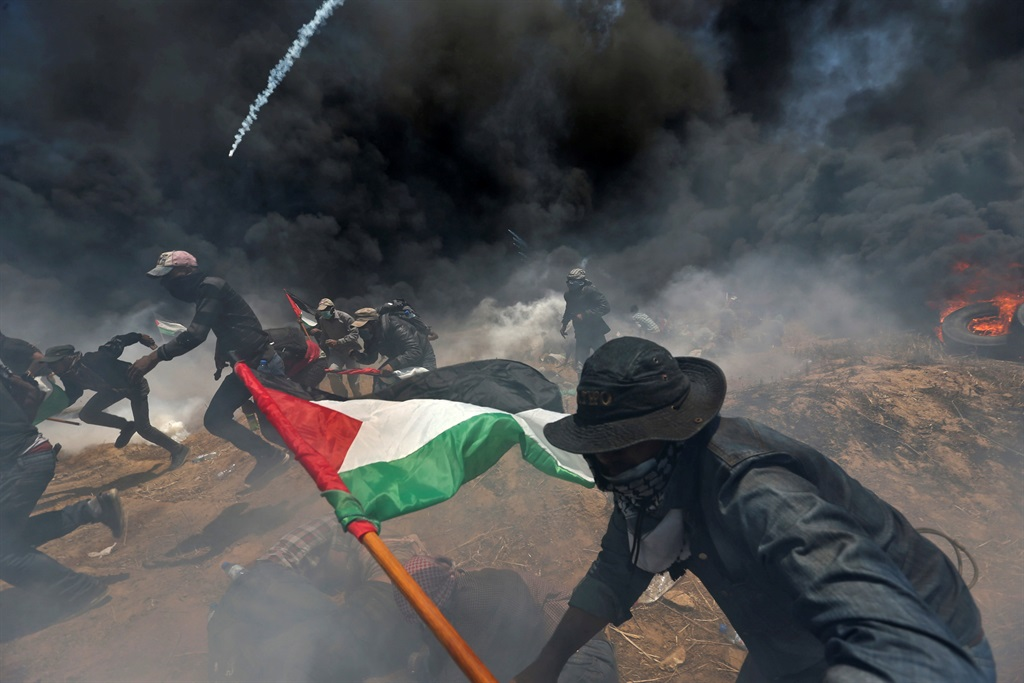 Palestinian demonstrators run for cover from Israeli fire and tear gas during a protest. Picture: Ibraheem Abu Mustafa/Reuters