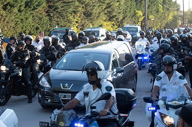 The hearse carrying the body of Argentine football legend Diego Maradona is surrounded by police officers on motorcycles as it enters Jardin Bellavista cemetery to be buried during a private ceremony on November 26, 2020 in Bellavista, Buenos Aires, Argentina. He is considered among the best footballers in history and lead his national team to the World Cup in 1986. President of Argentina Alberto Fernandez declared three days of national mourning.