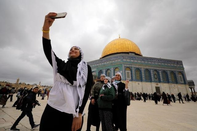 Worshippers take a selfie at the compound known to