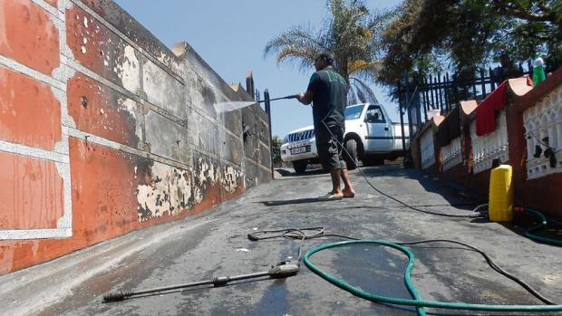 The taxi owner's son, Kaveer, cleaning the burned wall at the scene of an alleged petrol bombing that burned two vehicles.
