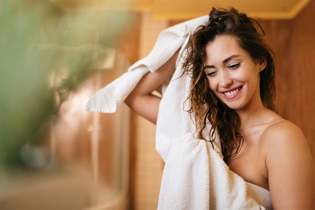 Young beautiful woman using towel and drying her h